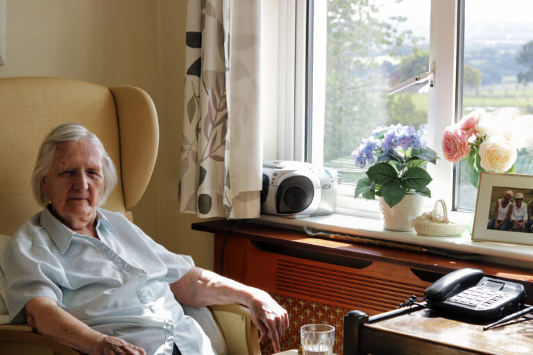 Roselands Residential Home resident seating in her room